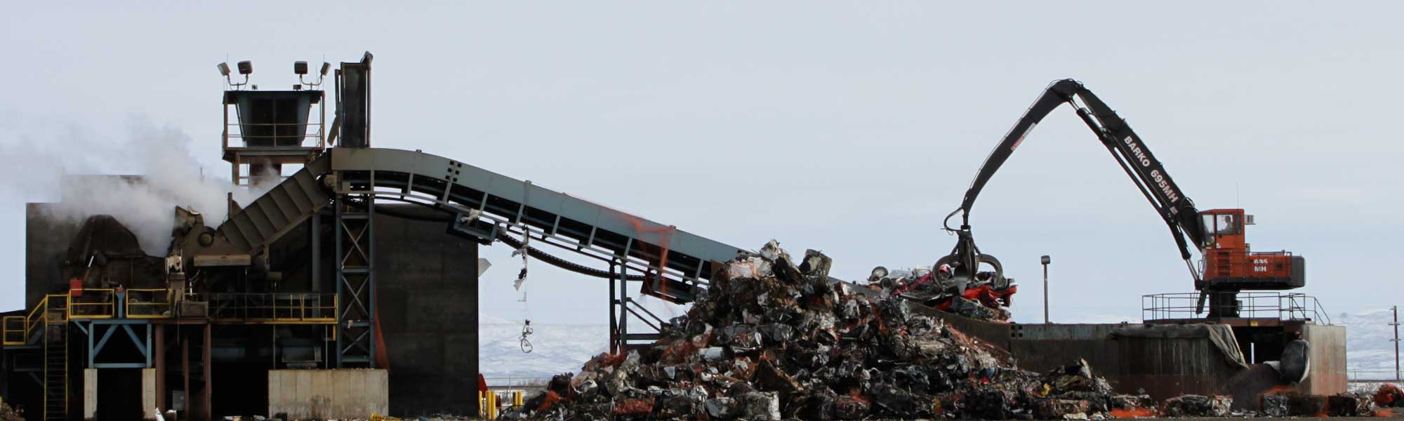 more scrap metal being moved at large recycling center