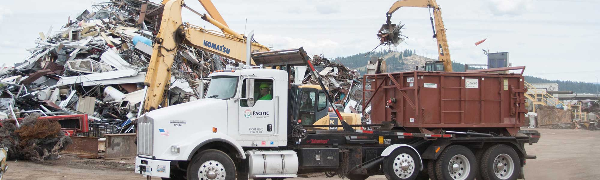 scrap metal yard with workers moving scrap metal